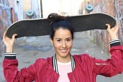 Retrato de la mujer hermosa feliz con el pelo sano atractivo largo en la chaqueta roja del bombardero que sostiene su monopatín q Imagen de archivo