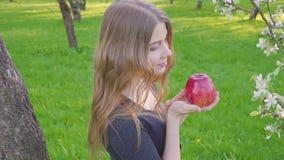 Retrato de la mujer hermosa joven de la cara que sostiene la manzana en la naturaleza floreciente del verano del fondo del manzan almacen de metraje de vídeo