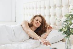 Retrato de la mujer hermosa joven con el pelo rizado que está en su cama por mañana, estirando su brazo para apagar el despertado fotos de archivo