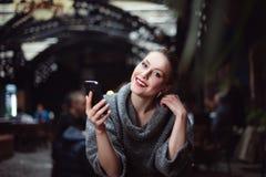 Retrato de la mujer hermosa joven con el teléfono elegante Fotos de archivo libres de regalías