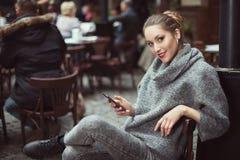Retrato de la mujer hermosa joven con el teléfono elegante Imagenes de archivo