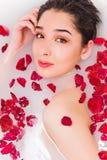 Retrato de la mujer hermosa joven con las flores y los pétalos color de rosa rojos en el baño de la espuma