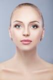 Retrato de la mujer hermosa joven con los ojos azules en fondo azul Imagen de archivo libre de regalías