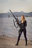 Retrato de la mujer hermosa joven con un arma Imágenes de archivo libres de regalías