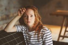 Retrato de la mujer hermosa joven del pelirrojo que se relaja en casa por la tarde acogedora del invierno del ot del otoño Foto de archivo libre de regalías