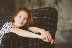Retrato de la mujer hermosa joven del pelirrojo que se relaja en casa por la tarde acogedora del invierno del ot del otoño Imágenes de archivo libres de regalías