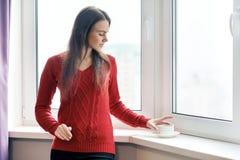 Retrato de la mujer hermosa joven en café de consumición del suéter rojo Situación femenina cerca de la ventana en rascacielos po fotos de archivo