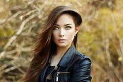 Retrato de la mujer hermosa joven en la chaqueta de cuero foto de archivo