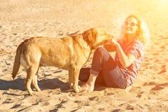 Retrato de la mujer hermosa joven en las gafas de sol que se sientan en la playa de la arena que abraza el perro del golden retri Fotos de archivo
