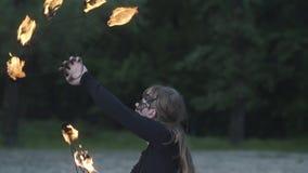 Retrato de la mujer hermosa joven en la máscara que realiza una demostración con la llama delante de árboles Artista experto del  metrajes