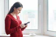 Retrato de la mujer hermosa joven en texto rojo de la lectura del suéter en smartphone y el café de consumición Situación de la m fotos de archivo