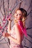 Retrato de la mujer hermosa joven en traje del ángel con triunfo rosado Fotos de archivo libres de regalías