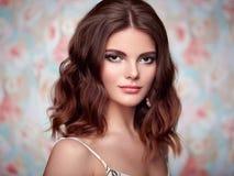 Retrato de la mujer hermosa joven en un fondo de flores Fotos de archivo