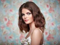Retrato de la mujer hermosa joven en un fondo de flores Imagenes de archivo