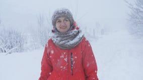Retrato de la mujer hermosa joven que camina en parque del invierno sobre fondo nevoso Mirada de la cámara en fondo del invierno metrajes