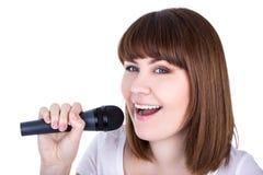 Retrato de la mujer hermosa joven que canta con el isolat del micrófono Imagen de archivo