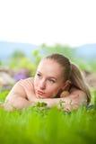 Retrato de la mujer hermosa joven que miente en hierba Imagen de archivo
