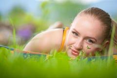 Retrato de la mujer hermosa joven que miente en hierba Imagen de archivo libre de regalías