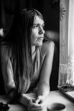 Retrato de la mujer hermosa joven que mira hacia fuera la ventana Foto de archivo libre de regalías