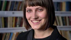 Retrato de la mujer hermosa joven que se coloca en biblioteca y que sonríe en la cámara, feliz y alegre metrajes