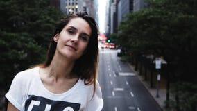 Retrato de la mujer hermosa joven que se coloca en el centro de la ciudad del puente adentro de Nueva York, América y mirando la  metrajes