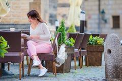 Retrato de la mujer hermosa joven que se sienta en un café de consumición al aire libre del café Turista feliz con el periódico e Imagen de archivo libre de regalías