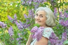 Retrato de la mujer hermosa mayor feliz con las lilas fotos de archivo