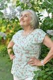 Retrato de la mujer hermosa mayor feliz en fondo de las lilas foto de archivo