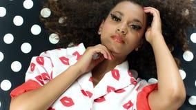 Retrato de la mujer hermosa negra joven que presenta en modelo de lunares blanco y negro almacen de metraje de vídeo