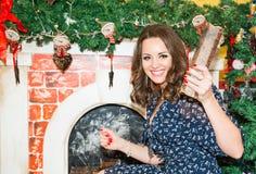 Retrato de la mujer hermosa por la chimenea en la Navidad Foto de archivo