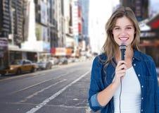 Retrato de la mujer hermosa que canta en el micrófono en la calle Foto de archivo