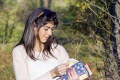 Retrato de la mujer hermosa que cuenta el dinero en su cartera Foto de archivo libre de regalías