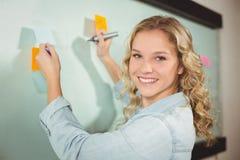 Retrato de la mujer hermosa que lleva a cabo la nota pegajosa mientras que escribe en el tablero de cristal Fotos de archivo