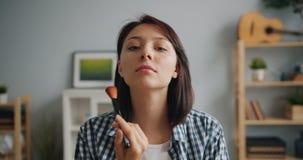 Retrato de la mujer hermosa que pone en el maquillaje que mira la cámara usando cepillo metrajes