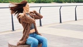 Retrato de la mujer hermosa que presenta en el r?o en la ciudad en d?a ventoso almacen de metraje de vídeo
