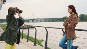 Retrato de la mujer hermosa que presenta en el r?o en la ciudad en d?a ventoso metrajes