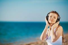 Retrato de la mujer hermosa que se sienta en la playa cerca del mar en los auriculares que escuchan la música Imagen de archivo libre de regalías