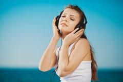 Retrato de la mujer hermosa que se sienta en la playa cerca del mar en los auriculares que escuchan la música Fotografía de archivo libre de regalías