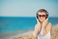 Retrato de la mujer hermosa que se sienta en la playa cerca del mar en los auriculares que escuchan la música Fotos de archivo libres de regalías