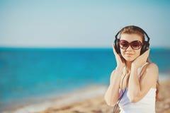 Retrato de la mujer hermosa que se sienta en la playa cerca del mar en los auriculares que escuchan la música Foto de archivo
