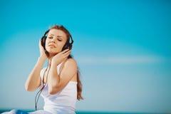 Retrato de la mujer hermosa que se sienta en la playa cerca del mar en los auriculares que escuchan la música Foto de archivo libre de regalías