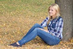 Retrato de la mujer hermosa que se sienta en parque del otoño Imagen de archivo