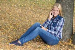 Retrato de la mujer hermosa que se sienta en parque del otoño con el teléfono Imagen de archivo