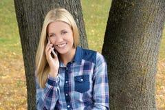 Retrato de la mujer hermosa que se sienta en parque del otoño y que llama b Imagenes de archivo