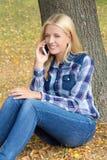 Retrato de la mujer hermosa que se sienta en parque del otoño y que usa pho Fotos de archivo