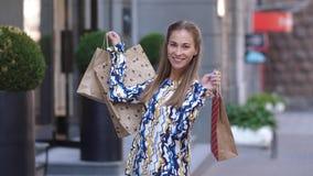 Retrato de la mujer hermosa que sonríe con los paquetes después de 4k que hace compras Cámara lenta almacen de video