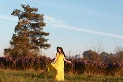 Retrato de la mujer hermosa sonriente joven en vestido amarillo en campo púrpura del prado del flor de la flor al aire libre en b foto de archivo libre de regalías