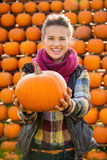 Retrato de la mujer hermosa sonriente que sostiene las calabazas en granja Fotos de archivo
