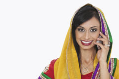 Retrato de la mujer india hermosa en llamada de teléfono de contestación del desgaste tradicional sobre el fondo blanco Imagen de archivo libre de regalías