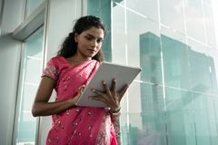 Retrato de la mujer india joven que usa una tableta al aire libre imagen de archivo libre de regalías